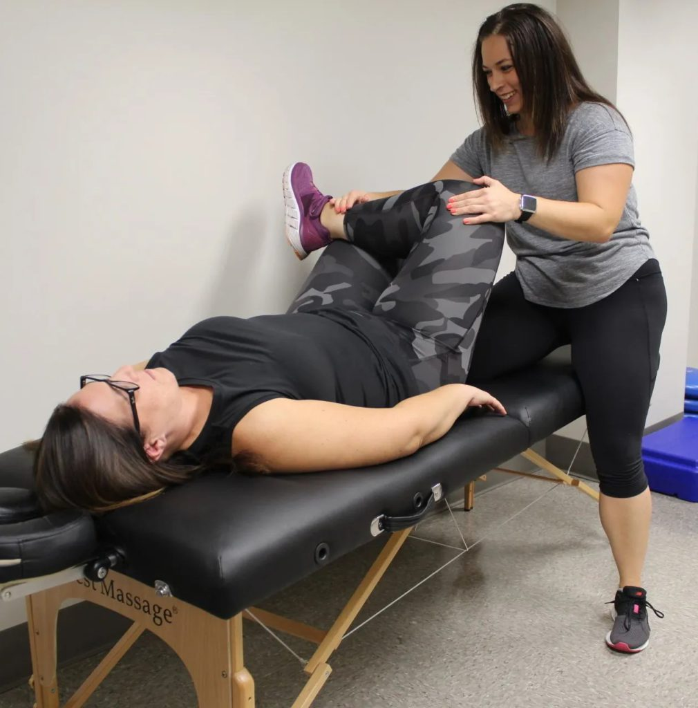Dr. Jen DeSantis helping a physical therapy patient stretch their leg
